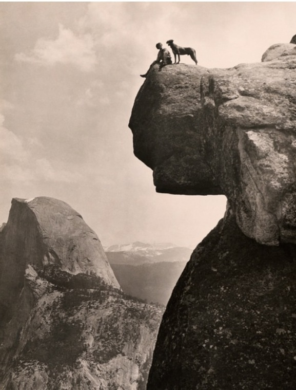 A man and his dog on the Overhanging Rock in Yosemite National Park, May 1924